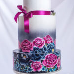 73790680 - large wedding cake ornamented in a traditional rustic style blue and purple roses and ribbon with the berries on top of a background of wavy fabric. food design. trends