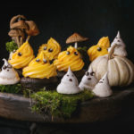 85469473 - halloween decorated sweet dessert table black cupcake with orange cream, white meringue ghosts with chocolate eyes, decor skulls and pumpkin on clay plate  over black background.