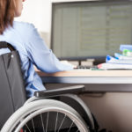 Disabled young business woman person sitting wheelchair working office desk computer