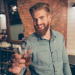 Casual men`s life. Cheers! Handsome young red bearded man in casual jeans outfit, drinking whiskey at the barber shop, enjoying and smiling